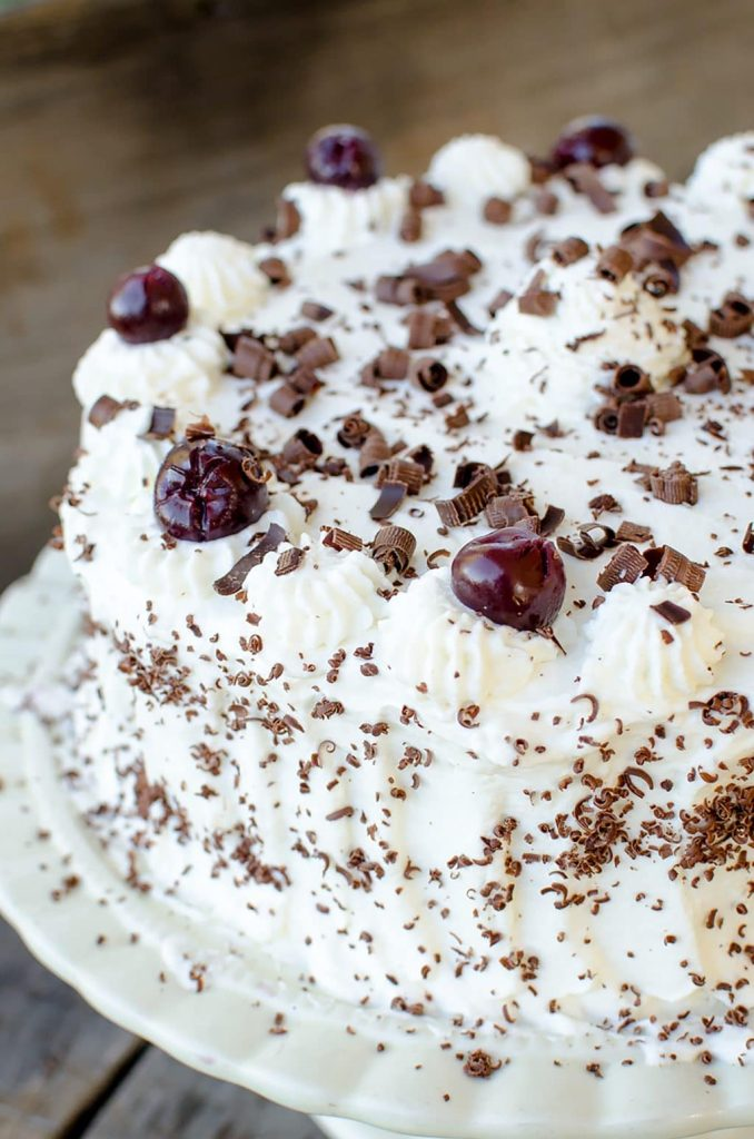 Chocolate Cherry Black Forest Cake Recipe A moist chocolate cake studded with cherries and frosted with whipped cream, Black Forest Cake baked from scratch is an impressive dessert.